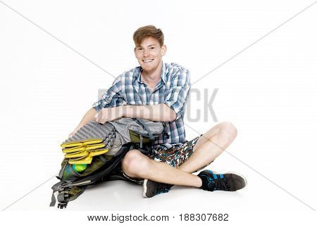 Young smiling tourist is sitting with backpack on the white background. traveler is preparing for hike