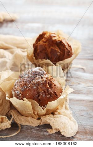 Tasty Muffins With Gauze Fabric On Wooden Table
