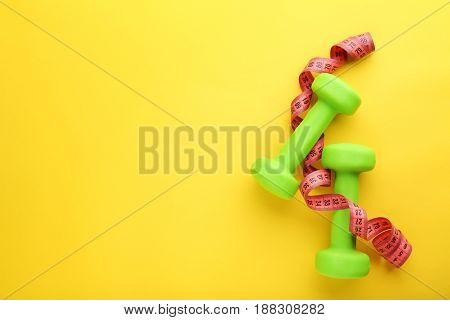 Green Dumbbells With Tape Measure On Yellow Background