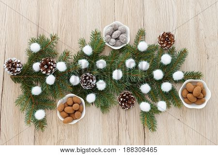 Chocolate coated almonds in small white bowls arranged around christmas decoration.