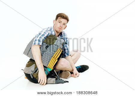 Young tourist is sitting with backpack on the white background. traveler is preparing for hike
