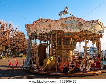 LAUSANNE, SWITZERLAND - DECEMBER 7, 2013: Old carousel on the embankment. Lake Geneva, Ouchy port, Lausanne, Switzerland