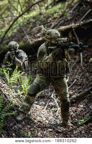 Group of soldiers on military operation in afternoon at forest