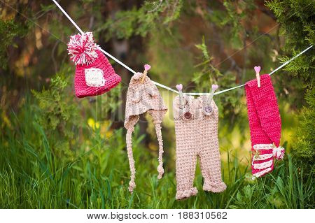 Knitted baby clothes hanging on rope outdoors over nature background.
