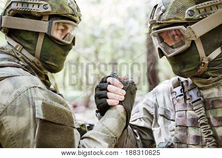 Two soldiers shaking hands in woods during day