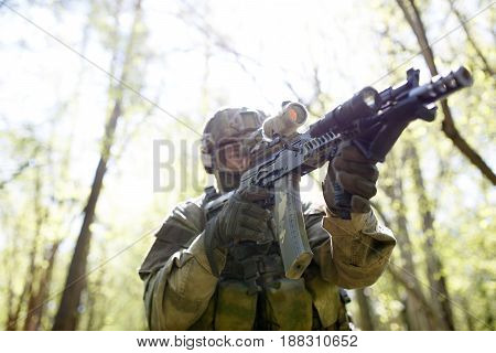 Soldier in helmet and with weapon in woods on military operation