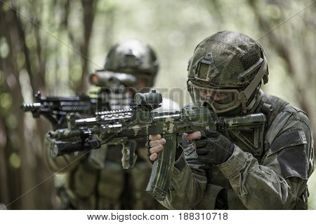Two men engaged in military game at woods during day