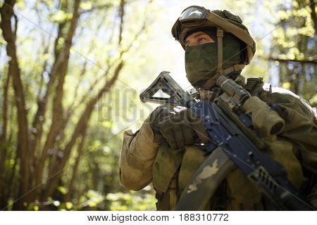 Military man in forest on reconnaissance by day