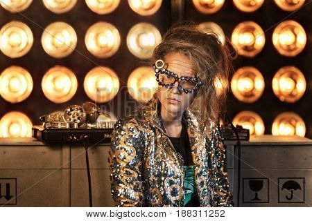 Young Girl With Makeup Of Senior Woman. Elderly Granny Playing A Dj Console.