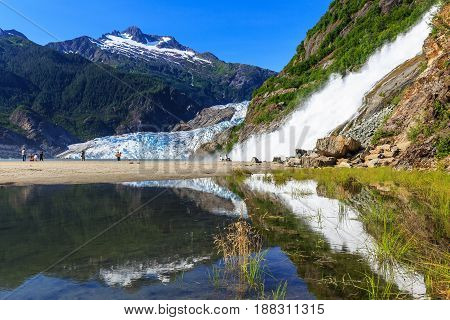 Juneau Alaska. Mendenhall Glacier Viewpoint with reflection in the lake and waterfall.
