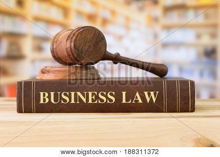 Business Law books with a judges gavel on desk in the library. Law education law books concept.