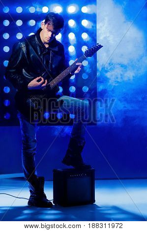 young attractive rock musician playing electric guitar and singing. Rock star on the  background of spotlights