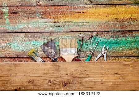 Spatula, brush, screwdrivers and pliers on a wooden background with space for text