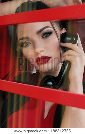 Beautiful Girl With Dark Hair And Red Lips Makeup, Posing In Red Phone Booth