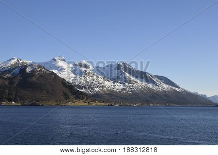 View over the sea with clear blue water and the village Bratland and snowy mountains in background against a clear blue sky picture from the North of Norway.