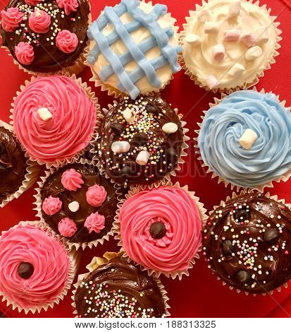 Decorated Cupcakes. Assorted chocolate and vanilla decorated cupcakes on red background