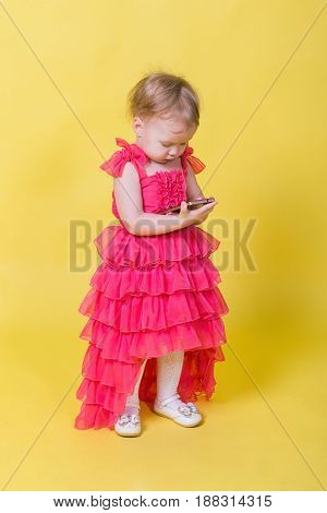 Girl toddler in a pink dress on a yellow background holding a smartphone.