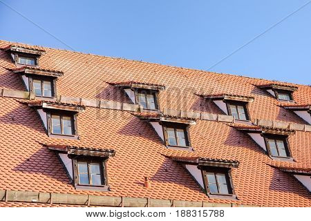 Tiled roof with mansard windows of attic rooms in antique European house