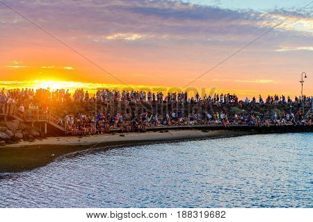 Melbourne Australia - December 28 2016: People spending time on St. Kilda Beach at sunset on a hot summer day Victoria Australia
