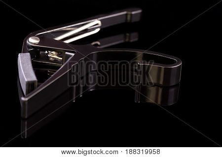 black spring clamp capo on a black background