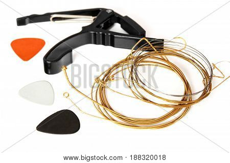 Twisted Copper guitar strings and capo and three plectrums on a white background