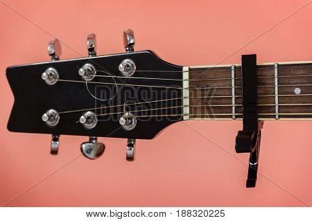 Black capo on a guitar on a peach Colour background