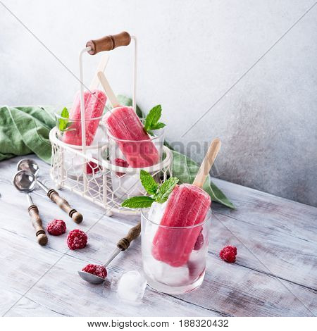Glass with raspberry popsicle, raspberries and mint on old white wooden background. Summer food concept