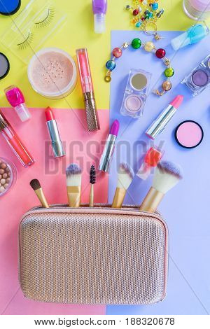 Colorful make up products with golden pursue material design top view flat lay scene