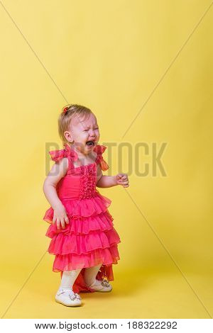 Little girl in pink dress crying on a yellow background.
