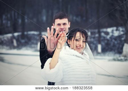 Happy Wedding Couple Raises Hands With Wedding Rings Standing In The Snow