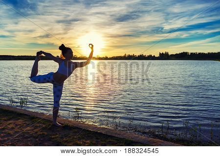 Young healthy woman practicing yoga on the beach at sunset