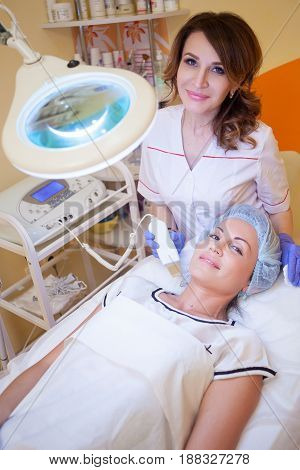 the doctor makes a woman patient procedures esthetician on face