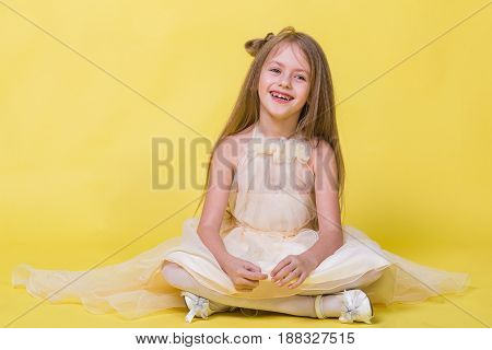 Teenager girl in a dress on a yellow background posing for the camera and sits on the floor.