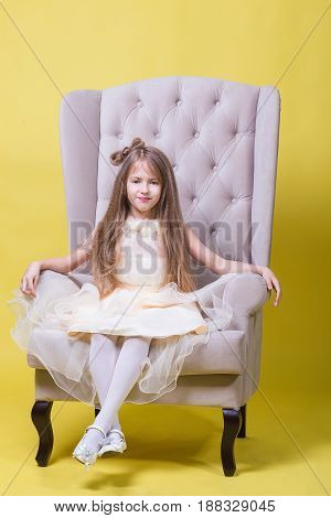 Teenager girl in a dress on a yellow background posing for the camera and sits on the chair.