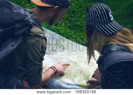 Young couple using a map on a adventure trip. Trip in a nature. Young happy people showing on a map. Traveler lifestyle