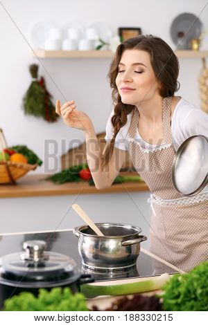Young woman in a dotted biege apron cooking soup in the kitchen. Food and health concept