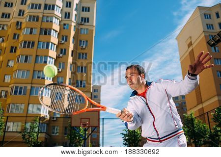 Man playing tennis outdoor, hot shot ball. Practicing tennis on the tennis court at sunny day.