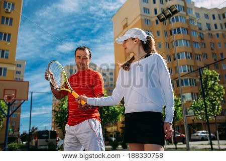 Man coach in sports clothing teaching young women how to properly hold a tennis racket at tennis court. Tennis training.