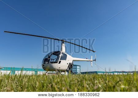 Small Robinson R22 light utility helicopter parked on grass airport. One of the world's most popular light helicopters with twin blades and a single engine.