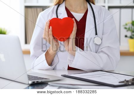 Unknown female doctor with stethoscope holding heart. Cardiology and medical care concept