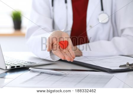 Unknown female doctor with stethoscope holding heart. Children's cardiology and medical care, stop abortation concept