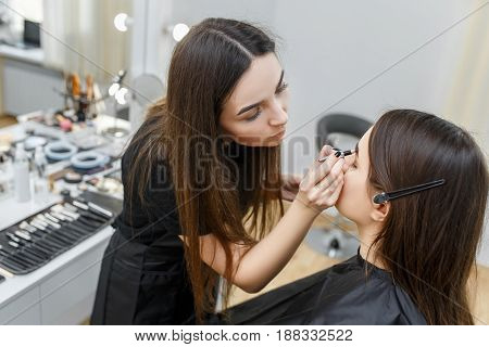 makeup artist contouring brows with eyebrow pencil.  Stylist is penciling eyebrow for young girl in beauty salon. Eyebrows shaping. Professional eyebrows makeup