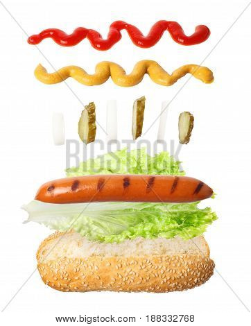 hot dog with hovering ingredients - sausage, lettuce, onion, pickle, ketchup and mustard. Hot-dog isolated on white background.  Fresh hot- dog with ingredients in the air. Flying fast food