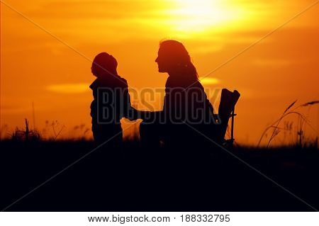 Silhouettes of young mother sitting on chair and son standing next to. Mom and son having fun outdoors on sunset time. Happy family relations concept.