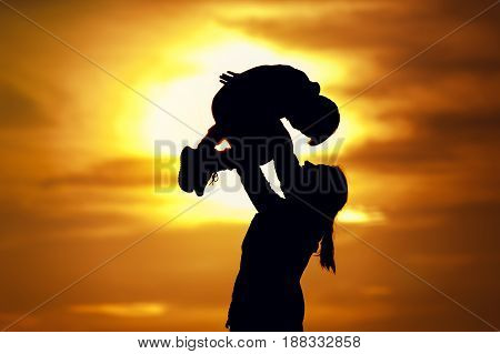 Happy family relationship. Silhouettes of young mother and little son having fun together outdoors. Woman raising up her kid against setting sun.