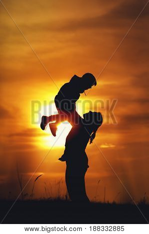 Happy family relationship. Silhouettes of young mother and little son having fun together outdoors. Woman playing with her kid against setting sun