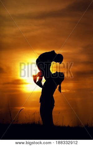 Silhouettes of young mother and little son having fun together outdoors. Woman playing with her kid, raising up boy against setting sun. Happy family concept.