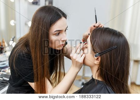 makeup artist contouring brows. Backstage photo as visagiste applying eyebrow makeup in beauty salon.  Eyebrows shaping