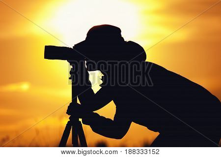 Silhouette of professional female photographer taking pictures with camera against setting sun. Travelling and tourism concept.