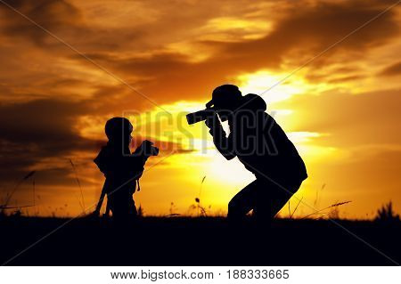 Happy family relationship. Silhouettes of young mother and little son having fun together outdoors. Woman photographing her childat setting sun light.
